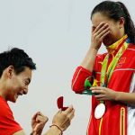 RIO DE JANEIRO, BRAZIL - AUGUST 14:  Chinese diver Qin Kai proposes to silver medalist He Zi of China on the podium during the medal ceremony for the Women's Diving 3m Springboard Final on Day 9 of the Rio 2016 Olympic Games at Maria Lenk Aquatics Centre on August 14, 2016 in Rio de Janeiro, Brazil.  (Photo by Clive Rose/Getty Images)