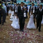 Palestinian girls accompany grooms as they walk separate from the brides during a mass wedding for 150 couples in Beit Lahiya town in the northern Gaza Strip July 20, 2015. The wedding was funded by al-Basheer Society for Relief and Development. REUTERS/Suhaib Salem